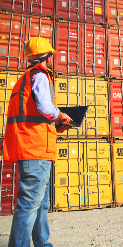 Employee in safety jacket controlling containers