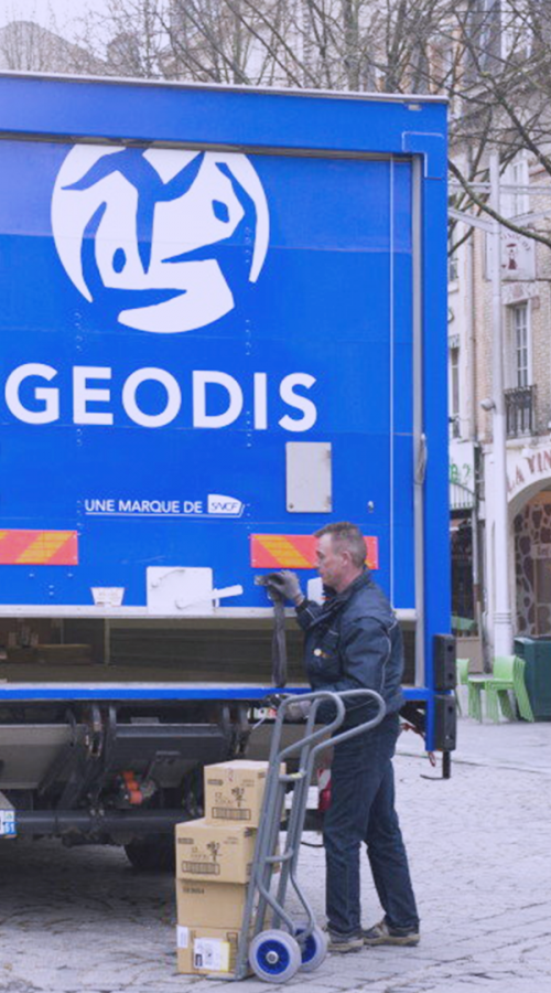 a delivery driver in front of a GEODIS truck