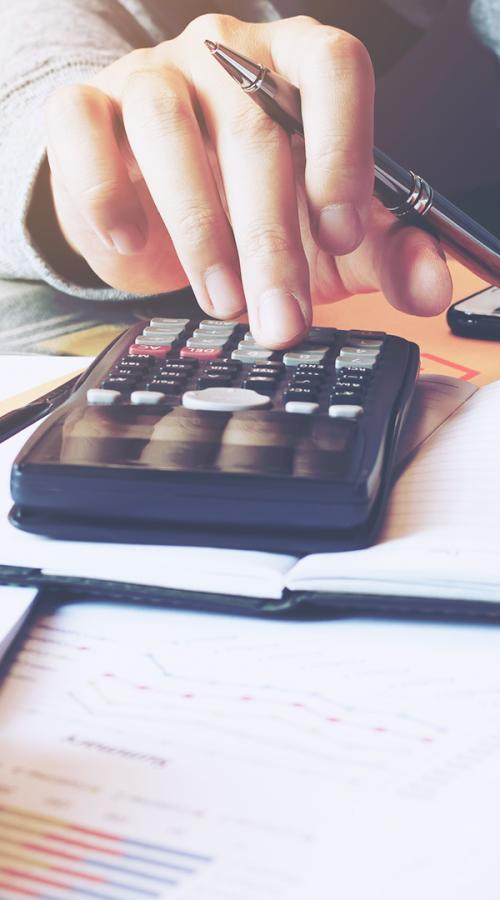 a man pays bills with a calculator