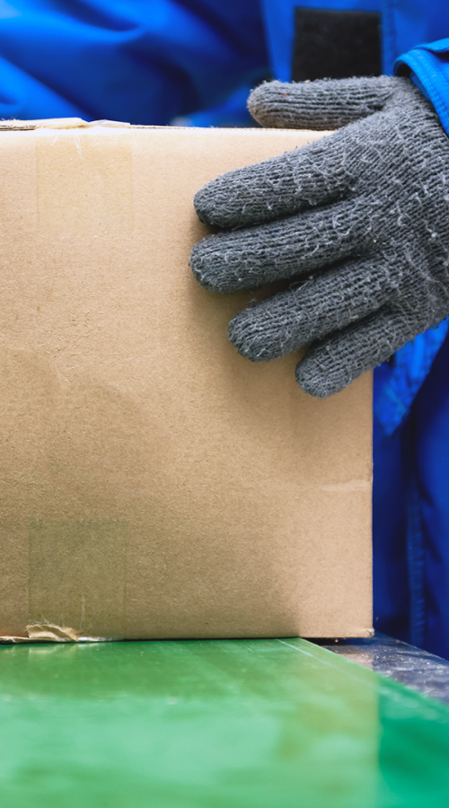 A GEODIS employee in glove takes a package