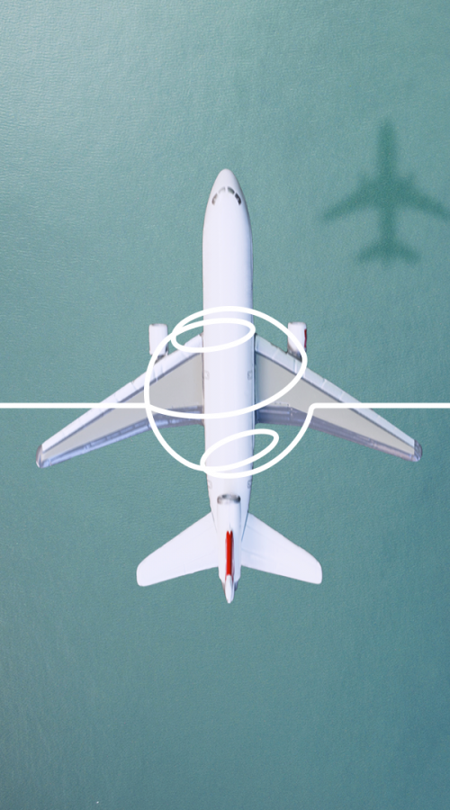 an airplane flies over a harbor with containers