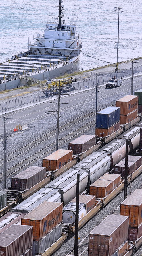 rail de train avec containers devant la mer