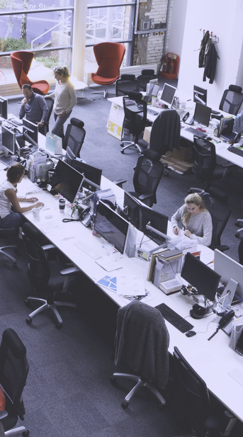 employees in an open space in front of their computer